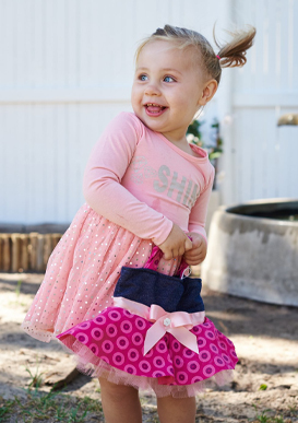A little girl laughing while holding her Bubs for Babes pink Shweshwe tutu handbag